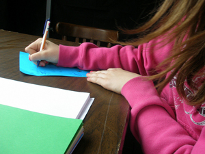 Photo of a girl's hands and part of a desk as she composes a letter