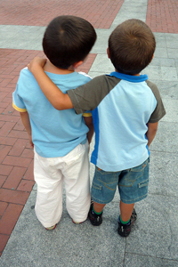 A photo of two small boys' backs as they stand and observe something out of the camera's view; One boy has his arm around the other one.