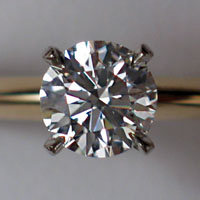 Photo of a four-pronged diamond taken up close to show the many prisms
