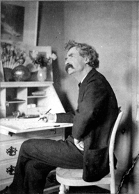 Mark Twain seated at his desk, looking upward as if in thought. He seems to have been interrupted while writing. The room shown in the old black and white photograph seems bare, but there are several vases filled with flowers on Twain's desk.