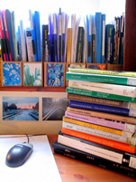 A photograph of a pile of textbooks on a desk next to a computer mouse