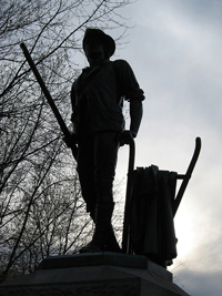 A photograph of the Minute Man monument in Concord, Massachusetts. It is a man holding onto a plow with one hand and a musket in the other.
