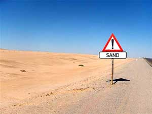 """photo of a sand and desert as far as the eye can see with a sign in the foreground that reads """"Sand"""""""