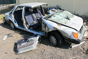 A photograph of a car that has been in an accident. The front end is crumpled up, all of the glass is gone, and the doors have been removed.