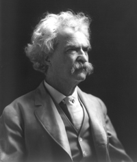 A photograph portrait of Mark Twain in his later years. He is wearing a suit and vest typical of the late 19th century.