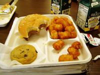 Photo of a half-eaten school lunch consisting of a burger, tater tots, and a chocolate chip cookie