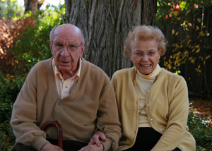 A photo of a pair of grandparents looking at the camera; they sit in front of a tree and wear sweaters.