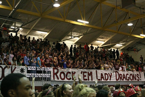 """A pep rally for Round Rock's Lady Dragons. The crowd is cheering and holding a huge """"Rock 'Em!"""" banner."""