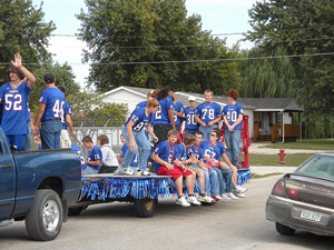 High School students in school colors riding on a float in a pep rally