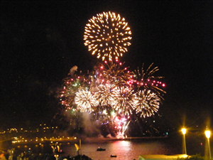 A photograph of a night time fireworks display over water