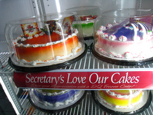"A photograph of cakes in a cooler. The is a sign between them that reads; ""Secretary's love our cakes."" There is an apostrophe in Secretary's which is an incorrect use of this punctuation."