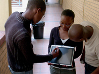 A photo of three African American students working on a tablet computer in the hall of a school building