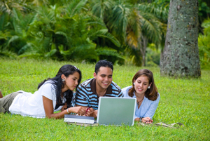 Three teenagers looking at a laptop in a grassy field