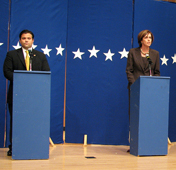 A photograph of a man and a woman during a political debate. Each is standing behind a podium.