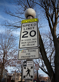 A photograph of a school zone sign that warns motorists not to use cell phones.
