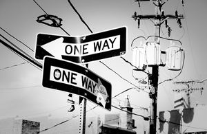A photograph of two 'one way' signs. One points left and the other points right.