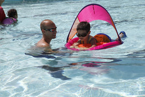 A photograph of a swim coach teaching a little boy how to swim using a flotation device.