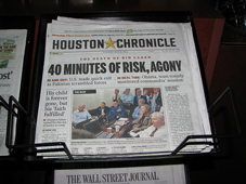 A photograph of a newspaper in a newspaper vendor's box. The paper is the Houston Chronicle.