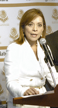 A female politician standing at a podium and speaking into a microphone.