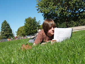 A photograph of a male student lying in the grass and reading a spiral bound text.
