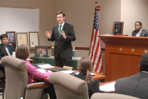A photograph of a male lawyer arguing a case before a jury in a court room