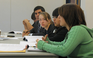 A photograph of a several young people sitting a table presenting or arguing a topic with documents and books spread out before them