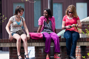 A photograph of three young women sitting on a bench. Two are talking and the other is looking at her phone.