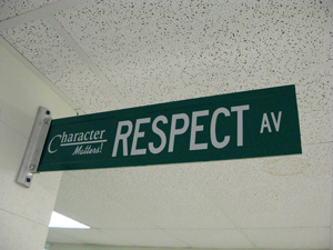 """A photograph of a street sign in a hallway. The sign reads """"Character Matters: Respect Avenue."""""""