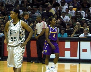 A photograph of two WNBA basketball players during a game. There are referees and a large seated crowd in the background