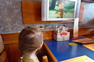 Photo of a girl watching Elmer Fudd while eating a corndog