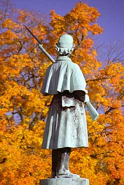 Sculpture of Civil War soldier surrounded by Autumn leaves