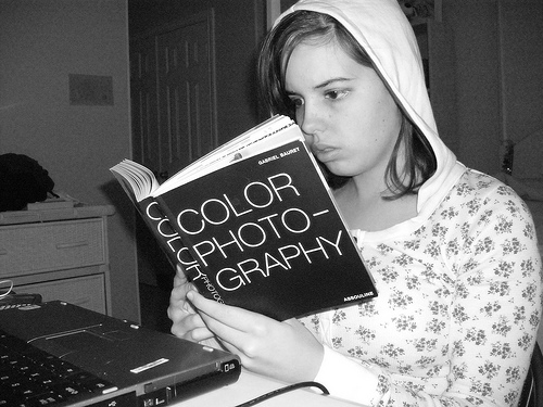 Black and white image of a young female reading a book.