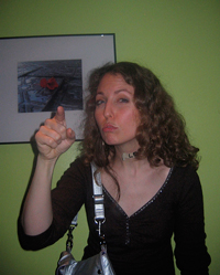 A photograph of a woman pointing with her index finger in a scolding fashion