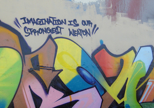 A photograph of graffiti art on a wall. Above the art is the phrase, 'imagination is our strongest weapon.'