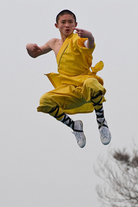 A photograph of a Kung Fu instructor jumping through the air.