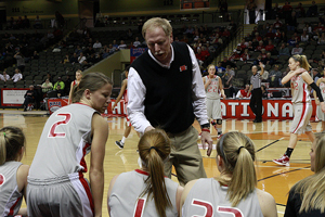 A photograph of a male coach talking to his girls' basketball team during a game.