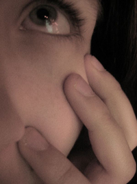 A photograph of a female student pondering. It is a close up of one eye with her fingers on her cheek.
