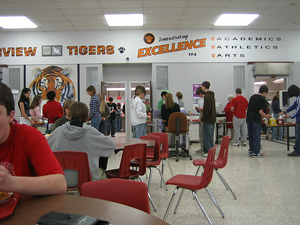 A photograph of a school cafeteria at lunch time.