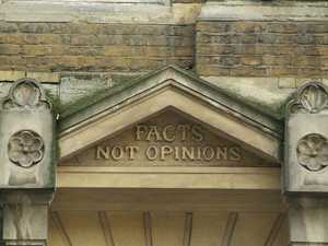 A photograph of an engraving on a building that reads, 'facts not opinions.'