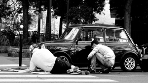 A photograph of a father and son talking while working on a car.
