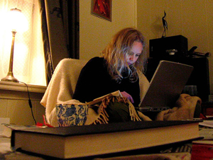 A photograph of a young woman sitting on a chair and looking at a laptop screen.