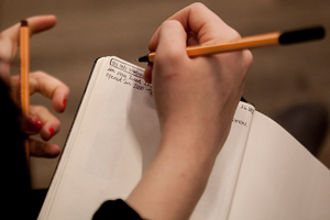 A photograph of a female student writing in a notebook.