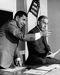 A photograph from the television series Dragnet. It shows the character Joe Friday and his partner, Bill Gannon in a courtroom.