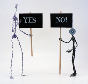"""A photograph of two wire sculptures that represent humans. They are holding signs: one reads """"Yes,"""" while the other reads """"No!"""""""