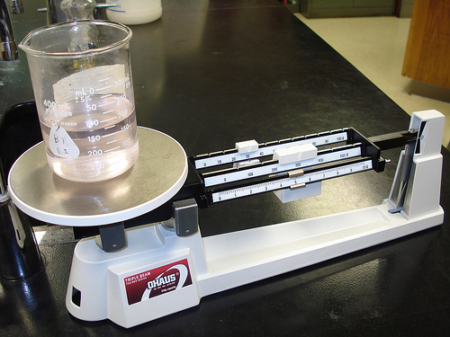 Liquid in a beaker. The beaker is sitting on a triple beam balance.