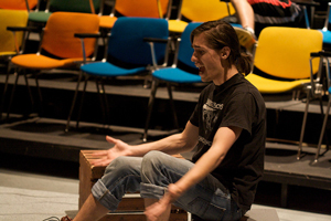 photo of a seated woman in casual clothes rehearsing a scene from a play in an empty theater; her arms stretch outward, palms are face up, and her face expresses a serious mood