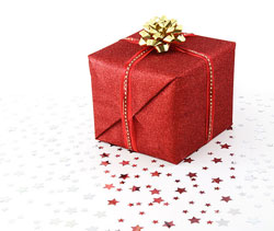 A photograph of a wrapped Christmas gift with star shaped glitter sprinkled around it