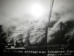 black and white photo of mountain-high clouds of dust just before rolling over several farm buildings; telephone and electrical wires stretch in different directions from leaning poles in the foreground; handwriting on photo reads 'Dust storm approaching Spearman, Texas April 14, 1935'