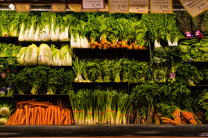 A photograph of a section of the vegetable aisle in a grocery store. There are radishes lettuces, parsley, carrots, and a variety of other vegetables
