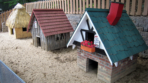 photo of three miniature houses built of straw, sticks, and brick